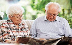 Пожилые люди читают газету, которую подписал дом престарелых «4 Сезона»